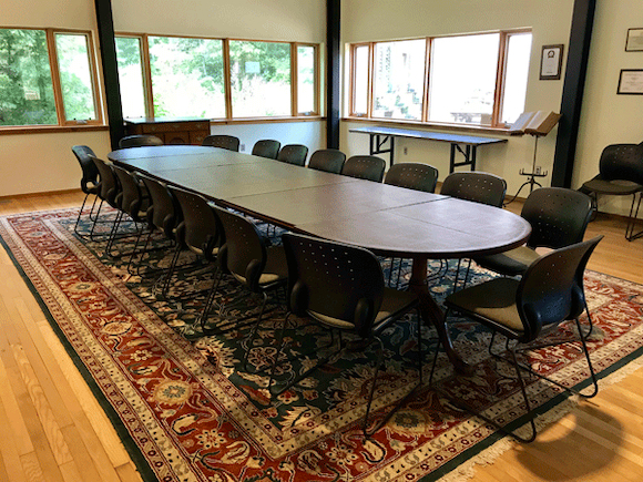The Bell Seminar Room, with lots of chairs arranged around a long table over an ornate rug.