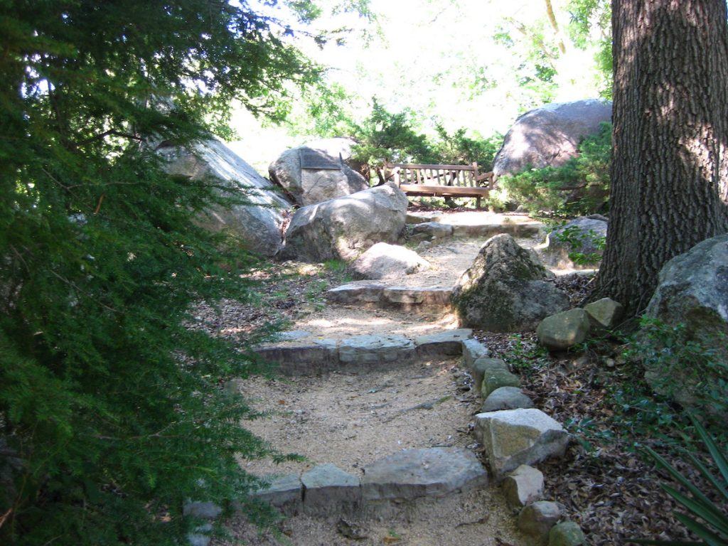 The Rocks in Chapel Hill. Stone steps and large rock outcrops with a wooden bench.