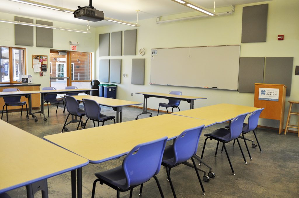 View of one of the Joslin classrooms, with tables arranged in a U-shape around a large whiteboard at the front of the room.