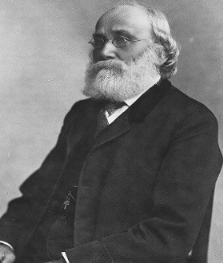 Black and white portrait of Charles T. Mohr. He has a bushy white beard, wire-rimmed glasses, and wears a dark suit.