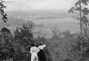 Black and white historical photo of Chapel Hill. Two ladies in dresses look down from the hill onto farmland.