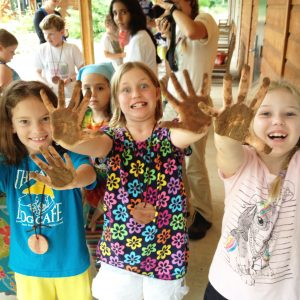 Kids hold up their muddy hands after making seed balls.
