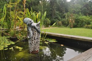 A ceramic sculpture of an octopus in a raised Water Garden bed.