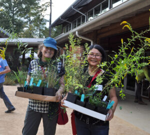 Two Garden members carry trays of plants from the Fall Plant Sale Members Preview night.