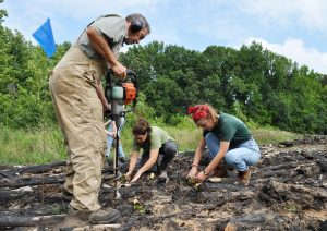 Johnny Randall drills holes into the ground for seedlings as NCBG interns plant them nearby