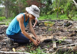 Lydie kneels on the ground to plant a seedling